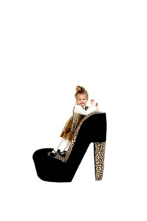 high heeled shoe: Hollywood has nothing over this adorable little girl model smiling happily   She is wearing a jungle print jumper with white turtle neck shirt and standing on a giant high heeled shoe    Stock Photo