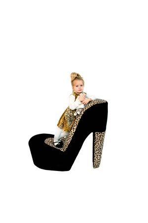 high heeled shoe: Hollywood has nothing over this adorable little girl model   She is wearing a jungle print jumper with white turtle neck shirt and standing on a giant high heeled shoe   She is hugging her stuffed toy and dreaming of Hollywood  Stock Photo
