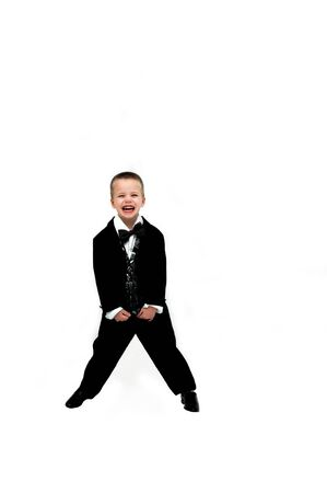he laughs: Little boy in tuxedo laughs hilariously   He is standing with feet spread holding the ends of his silver and black tuxedo vest