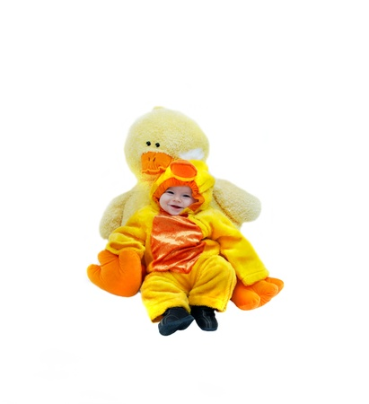 Baby dressed in baby duckling costume, cuddles with its mother counterpart, a stuffed giant yellow duck   Isolated on white  Stock Photo - 14910384