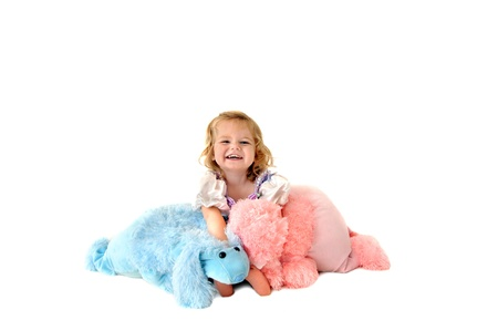 Little girl laughs happily as she cuddles with two large stuffed fuzzy toy poodles,  She is sitting in an all white room  photo