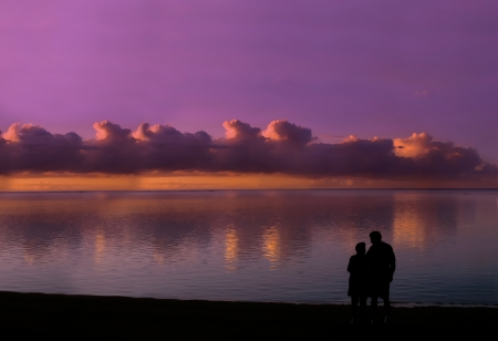 Older couple still in love and enjoying a sunset together, stand on the shores of Kauai, Hawaii and look into each other