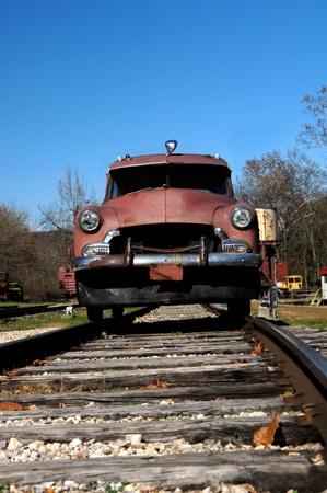 Automobile designed for transportation on railroad tracks sits on tracks under a blue sky  Vintage model Stock Photo - 14922409