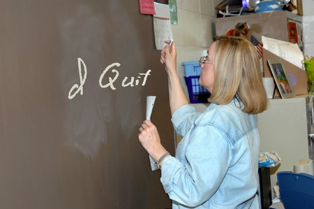 Experienced female teacher writes on classroom chalk board the words  I Quit    She is holding a piece of chalk in one hand and a paper in the other  photo