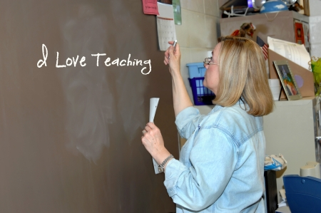 Female school teacher expresses her enjoyment of her job by writing  I love teaching   photo