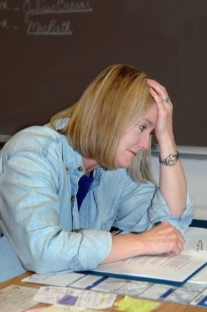 Female teacher overwhelmed with the stress of educating todays youth, leans her head in her hands and falls into negative thoughts   Blackboard and cluttered desk  photo