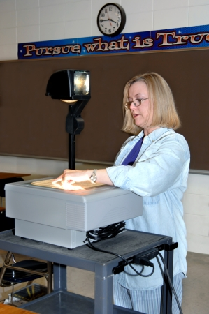 Female teacher uses an overhead projector to illustrate a lesson   She is dressed in a denim shirt and is wearing glasses