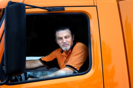 Big rig driver looks out the window of his orange truck while making a delivery   He is wearing orange