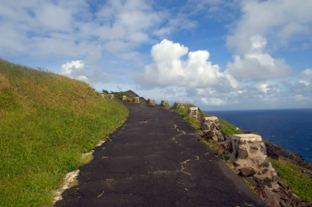 ascends: Cracked pavement road ascends the cliff trail to the Makapuu Lighthouse overlook   The sea bluff overlooks Hanauma Bay and Sandy Beach