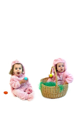 dressup: Twin girls dressed in pink Easter bunny costumes play in an all white room.  One is sitting with mouth open and Easter egg in hand.  The other is inside an Easter basket.