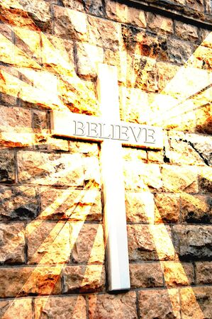 Stone wall has cross carved into it.  The cross throws rays of light and the word BELIEVE is emblazened across it.