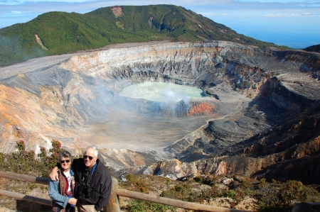 seeps: Retired American couple visit Poas Volcano National Park in Costa Rica.  The volcanic lake in the background is called Laguna Caliente.  Rugged volcano crater seeps acid fog.