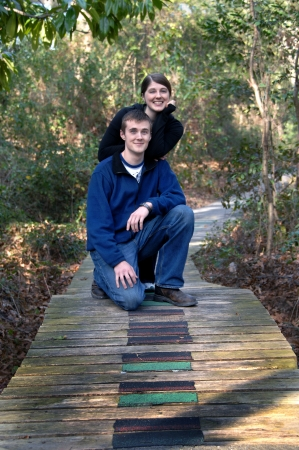Sister and brother pause in their amble through the South Arkansas Arboretum in El Dorado, Arkansas   Brother kneels on wooden footbridge and sister leans on his shoulder  photo