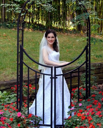 Bride stands behind a black metal arch and gate   Red flowers bloom at her feet and she glows with a happy smile  photo