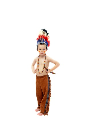 Little boy, dressed in fringed leggings and feathered headdress, carries a wooden bow and stand in all white room   He is wearing an indian costume  Stock Photo - 14910378