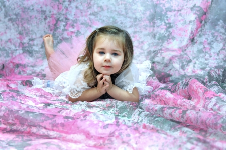 Baby ballerina lays on a floor of pink and grey   She is barefoot and she leans her head on her hands   Her expression is thoughtful