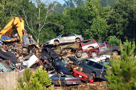 A pile of wrecked cars and auto bodies are crushed and stacked for spare parts or metal salvage   Trees and weeds surround pile  Banco de Imagens