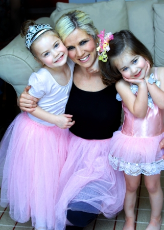 Mother hugs daughters close for a hug   They are all three wearing ballerina costumes and playing dress-up at home