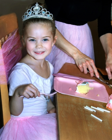 Beautiful little girl is enjoying her ballerina birthday party   She is wearing a crown and pink tutu   Her fork is poised ready to eat her slice of cake  photo