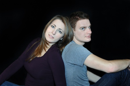 somber: Black background frames young couple   Both are unsmiling and somber   They are dressed casual in jeans