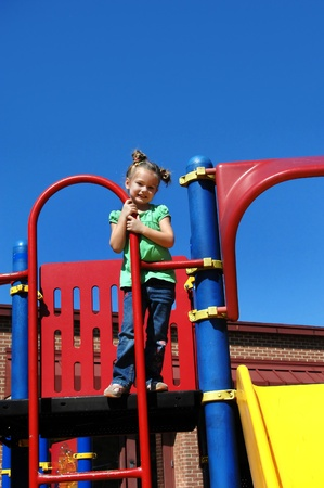 playground equipment: Little girl stands on playground equipment at her school   She is enjoying a sunny day outside playing and exercising