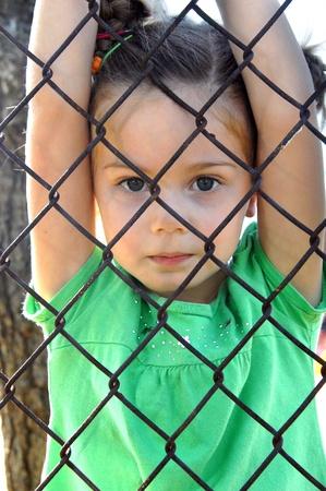 chainlinked: Klein meisje hangt van binnen de keten verbonden speelplaats van haar school De metalen hek dient als bescherming tegen de buitenwereld