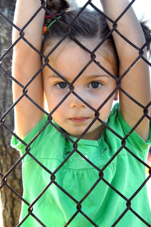 linked: Small girl hangs from inside the chain linked playground of her school   The metal fence serves as protection from the outside world