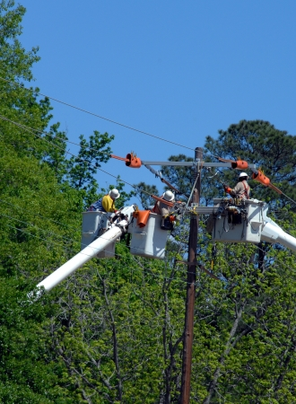 Three linemen perform maintenace on a utility pole   Three buckets lift them to the top of the pole as they replace parts and fix problems