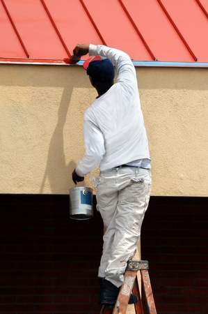 Man stands on top step of ladder while painting roof line on office building in downtown Albuquerque, New Mexico   He is holding a paint can and spreading paint with brush