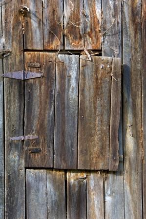 Verweerd hout, leer en ijzer scharnieren houden de vergrijzing van de loft deur naar deze oude schuur bedekt met roestige en gebogen spijkers Stockfoto