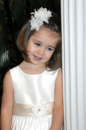 agachado: Niña de las flores en la boda se apoya en un pilar blanco Ella lleva un vestido blanco y un arco de flores Ella está agachando la cabeza con timidez Foto de archivo