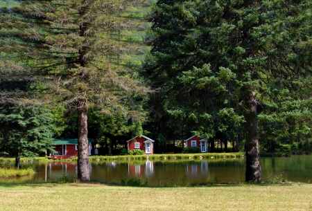 Nine Mile Creek can be enjoyed in rustic red cabins   Reflection shows in the calm still waters of small lake in front of this property