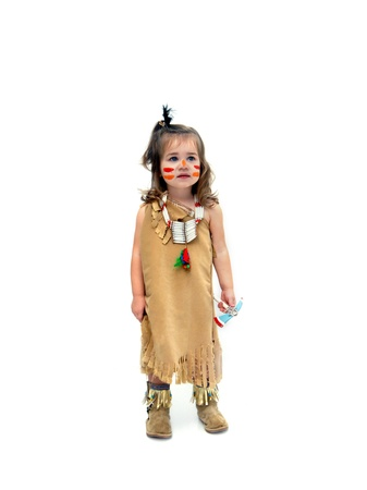 Little girl, dressed as an indian child, stands in an all white room   She is carrying a tomahawk and wearing a beaded necklace   Her face is smeared with read and orange paint