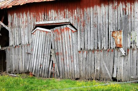 Sagging, double doors barely hang on their hinges on this rustic barn   Wood is weathered and once painted red   Gaping holes show bare boards on interior Stock Photo - 14922555