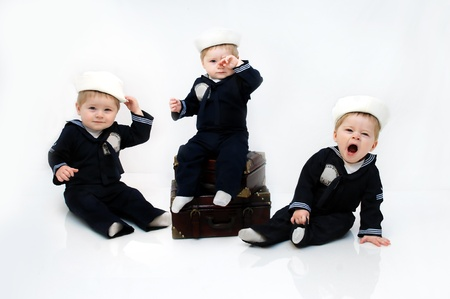Adorable baby boy wears a navy serviceman costume   He is yawning and leaning on one hand in an all white room with space for personalization  photo