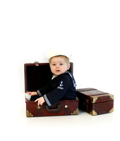 go inside: Baby boy, wearing a navy service costume, sits inside a brown suitcase   He is preparing to go serve his country in the navy  Stock Photo