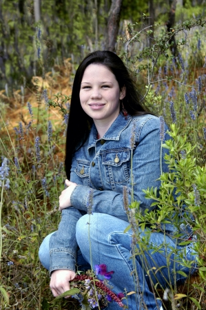 denim jacket: Teenager visiting Mexico enjoys an afternoon picking wildflowers   She is wearing a denim jacket and jeans and is kneeling surrounded by wildflowers                         Stock Photo