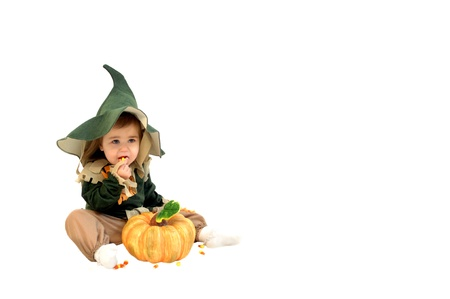 Tiny scarecrow sits in an all white room and chows down on candy corn   A single pumpkin sits in front this adorable little girl  photo