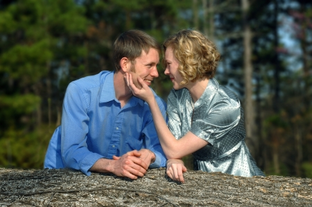 Young couple look affectionately into each others eyes   Sunny afternoon in the country with a fallen tree for a photo prop  photo