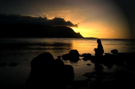 La mujer se sienta solo en una playa en Princeville, Kauai y observa la puesta de sol detrás de un banco de nubes y las montañas de Kauai. Puesta del sol tiñe el cielo y las aguas de un oro brillante.