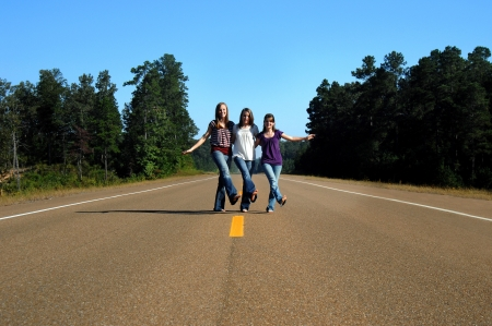 Three senior girls dance down the middle of the road.  High School is finished and they are ready to start their journey into their future. Stock Photo - 14915740