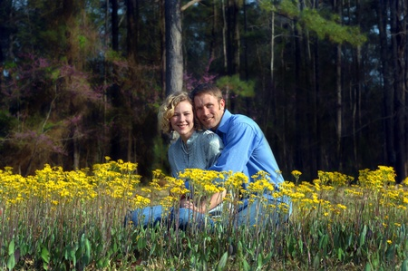 Field of yellow flowers surround young loving couple.  Both are smiling and dressed casual. photo