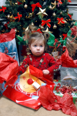 It is not in there   Little toddler looks disappointed in the contents of her Christmas bag   She is still wearing her Christmas morning pajamas and holding open a decorative gift bag Stock Photo - 14914374