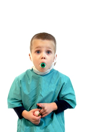 Little physician has an eye in his mouth and one in his hand   He is wearing a scrub and operating mask   Sign on scrub says  Dr  Eye Care   photo