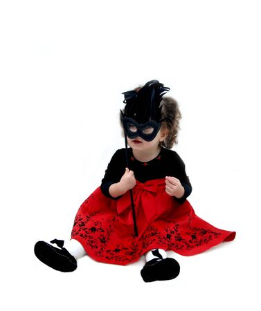 Baby plays with mask for Mardi Gras Parade   She is wearing a bright red dress and holding a black mask with black feathers  Stock Photo - 14914087