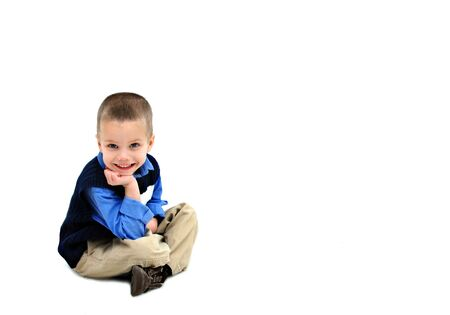 khakis: Little boy sits in an all white room   He is dressed in khakis and a navy sweater vest   He is grinning from ear to ear