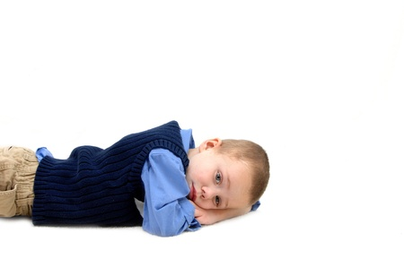 khakis: Small boy lays on the floor in an all white room   He is resting his head on his arms and has a sad and worried expression on his face   He is wearing khakis and navy sweater vest