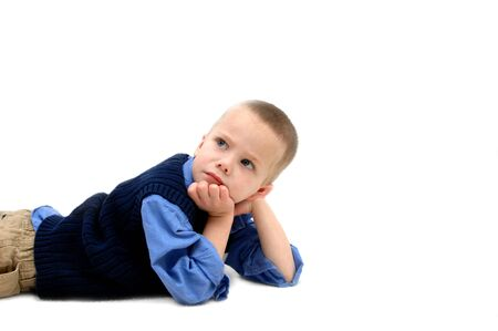khakis: Small boy puts chin in hand and ponders over his childhood concerns   He is laying in an all white room and room is left for personalization