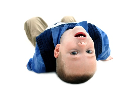 he is different: Small boy turns his world upside down to get a different and new view   He is laying on an all white floor with his head tilted backwards   He is wearing khakis and navy blue sweater