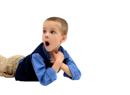 khakis: Little boy lays on the floor propped on his elbows   His mouth is open and he is staring in amazement   He is wearing a sweater vest, khakis and blue shirt   Isolation and space for personalization  Stock Photo